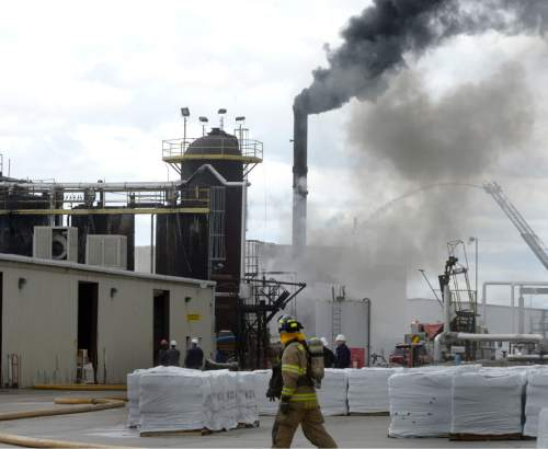 Al Hartmann  |  The Salt Lake Tribune Firefighters battle a smoky fire from an asphalt container at an industrial refinery at 2600 S. 1600 W. in Woods Cross Tuesday April 26.