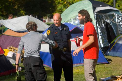 Al Hartmann     Tribune file photo Salt Lake City Deputy Police Chief Mike Brown, center, shakes hands with one of the the Occupy Wall Street-Salt Lake protesters as Aharon-Ben-Or, one of the original organizers, looks on in 2011.