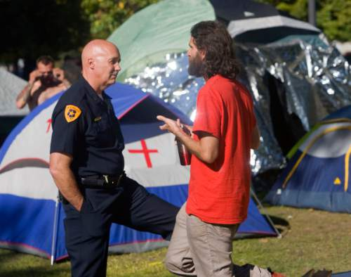 Al Hartmann     Tribune file photo Then Salt Lake City Deputy Police Chief Mike Brown talks with Aharon-Ben-Or, right, one of the original organizers of the  Occupy Wall Street-Salt Lake protest in Pioneer Park in 2011.