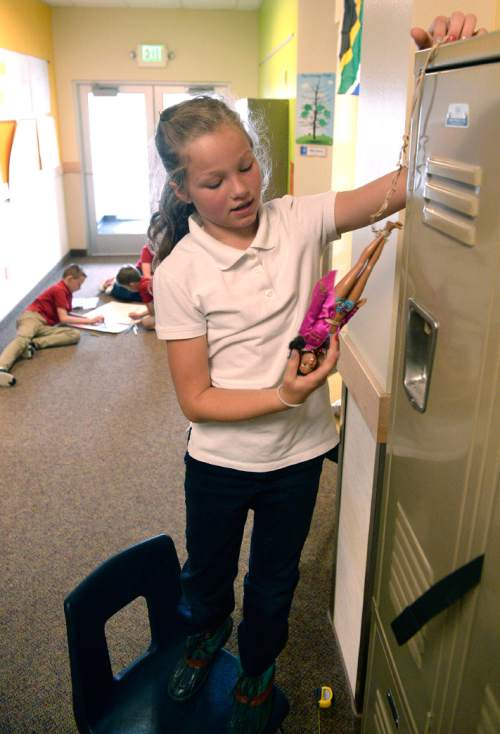Al Hartmann  |  The Salt Lake Tribune Fifth grader Kate Youngquist catches her Barbie doll after it takes a fall from the top of a locker at Wasatch Peak Academy in North Salt Lake.  Not to worry.  Barbie was attached to a series of rubber bands to simulate a bungee jump.  Youngquist had to measure weight, velocity, and amount of stretch of the rubber bands using her algebra skills.   A new report by the Utah Foundation says that charter schools receive less funding than school district schools, but charter advantages make it difficult to determine if the funding is inequitable.
