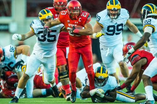 Chris Detrick  |  The Salt Lake Tribune Utah Utes running back Devontae Booker (23) runs past Michigan Wolverines linebacker Joe Bolden (35) and Michigan Wolverines safety Delano Hill (44) during the first half of the game at Rice-Eccles Stadium Thursday September 3, 2015.  Utah is winning 10-3 at halftime.
