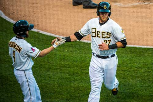 Chris Detrick  |  The Salt Lake Tribune Salt Lake Bees catcher Jett Bandy (27) celebrates with Salt Lake Bees left fielder Shane Robinson (4) after he scored a run during the game at Smith's Ballpark Thursday April 7, 2016.