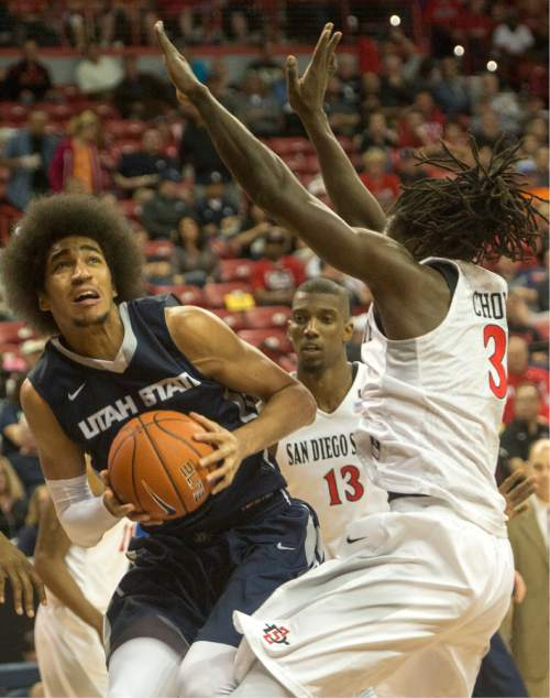 Rick Egan  |  The Salt Lake Tribune  Utah State Aggies forward Jalen Moore (14) looks for a shot, as San Diego State Aztecs forward Angelo Chol (3) defends, in Mountain West Tournament action, The Utah State Aggies vs. San Diego State Aztecs, at the Thomas and Mack Center in Las Vegas, Thursday, March 10, 2016.