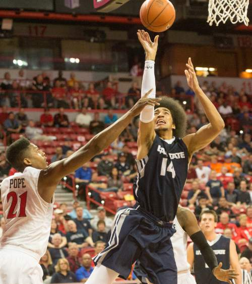 Rick Egan  |  The Salt Lake Tribune  Utah State Aggies forward Jalen Moore (14) takes a shot, as San Diego State Aztecs forward Malik Pope (21) defends, in Mountain West Tournament action, The Utah State Aggies vs. San Diego State Aztecs, at the Thomas and Mack Center in Las Vegas, Thursday, March 10, 2016.