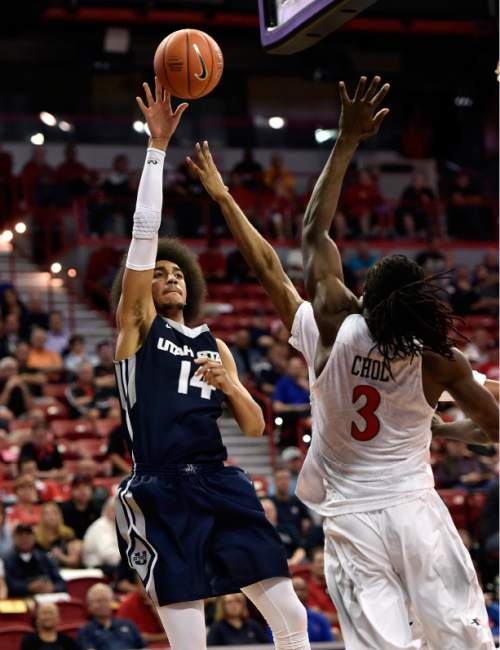 Utah State's Jalen Moore (14) shoots agains San Diego State's Angelo Chol (3) during the second half of an NCAA college basketball game at the Mountain West Conference men's tournament Thursday, March 10, 2016, in Las Vegas. San Diego State won 71-65. (AP Photo/David Becker)
