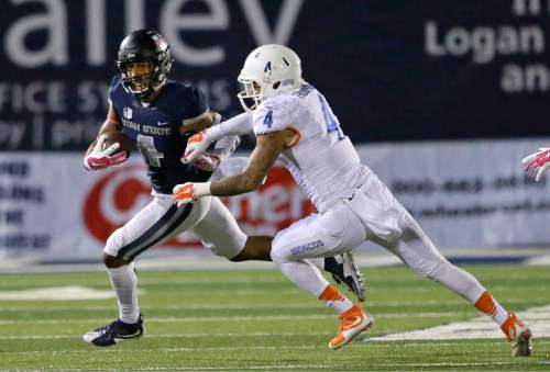 Utah State wide receiver Hunter Sharp, left, out runs Boise State safety Darian Thompson during the second half during an NCAA college football game  Friday, Oct. 16, 2015, in Logan, Utah. Utah State won 52-26. (AP Photo/Rick Bowmer)
