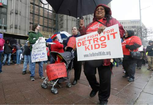Detroit teachers march outside the district headquarters, Monday, May 2, 2016, in Detroit. Detroit Public Schools transition manager Steven Rhodes says 45,628 of approximately 46,000 students were forced to miss classes Monday as 1,562 teachers called in sick. The mass sick-out has forced the district to close 94 of its 97 schools. Detroit's schools are expected to be out of cash starting July 1. The state earlier gave the district $48.7 million in emergency funding to keep it open through June 30 as the Legislature considers a $720 million restructuring plan. (AP Photo/Carlos Osorio)