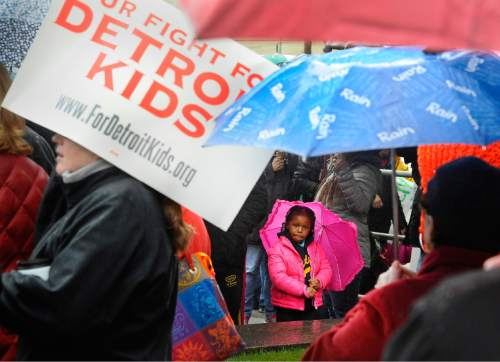 Jordyn Dearing, 5, a Nichols Elementary School student, with her mother who is a teacher there, attends a Detroit Federation of Teachers rally outside Detroit Public Schools offices at the Fisher Building in Detroit, on Monday, May 2, 2016.  The district's state-appointed transition manager Steven Rhodes says 45,628 of approximately 46,000 students were forced to miss classes Monday as 1,562 teachers called in sick. Detroit's schools are expected to be out of cash starting July 1.  (Daniel Mears/The Detroit News via AP)