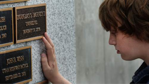 Steve Griffin / The Salt Lake Tribune  Jack Barney rests his fingertips on a bronze plaque with his father, Unified Police Officer Douglas S. Barney's  name engraved on it, as the Utah law enforcement community held its annual memorial to police officers killed in the line of duty during the previous year at the State Capitol, Utah Law Enforcement Memorial, West lawn in Salt Lake CityThursday May 5, 2016. Officer Barney was murdered January 17, 2016 while investigating a hit and run crash in Holladay. A second officer, Jon Richey, was wounded but recovered.