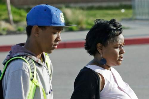 "Holly Frye and her son D.J. pose for a photograph at the South Ogden Junior High School Wednesday, May 4, 2016, in South Ogden, Utah. An official says a white Utah teacher violated school district policy by using a racially charged word in his junior high class. History teacher Douglas Barker used the N-word before showing his class of 8th graders the Civil War movie ""Glory."" Parent Holly Frye said her 14-year-old son doesn't feel safe at school after the experience last month. (AP Photo/Rick Bowmer)"