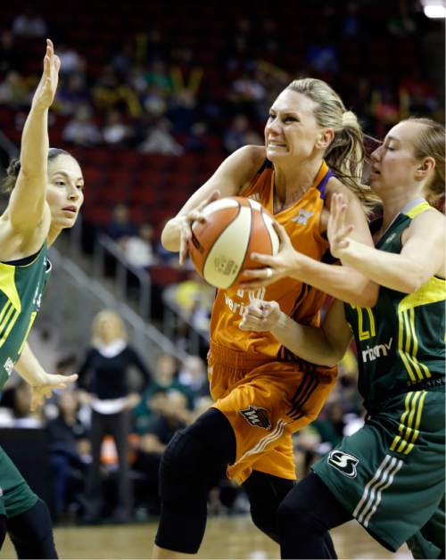 Phoenix Mercury's Penny Taylor, center, drives between Seattle Storm's Sue Bird, left, and Lexi Eaton Rydalch in the first half of a WNBA preseason basketball game Wednesday, May 4, 2016, in Seattle. (AP Photo/Elaine Thompson)