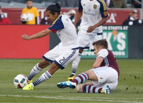 Real Salt Lake defender Tony Beltran, left, kicks the ball as Colorado Rapids forward Kevin Doyle defends in the first half of an MLS soccer game in Commerce City, Colo., late Saturday, May 7, 2016. (AP Photo/David Zalubowski)
