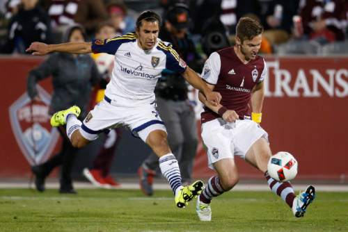 Real Salt Lake defender Tony Beltran, left, pursues Colorado Rapids forward Kevin Doyle as he takes a shot in the second half of an MLS soccer game in Commerce City, Colo., late Saturday, May 7, 2016. The Rapids won 1-0. (AP Photo/David Zalubowski)