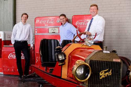 Trent Nelson  |  The Salt Lake Tribune Auctioneer Rob Olson, right, and his sons David, left, and Robert pose for a photo at Erkelens & Olson, which is celebrating its 40th year in the auction business. Salt Lake City, Friday April 22, 2016. In the photo are vintage Coca-Cola machines and a 1913 Model T.