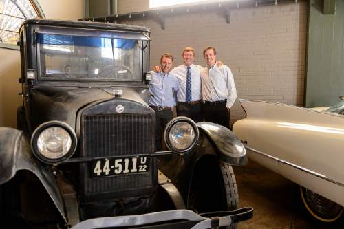 Trent Nelson  |  The Salt Lake Tribune Auctioneer Rob Olson, right, and his sons Robert, left, and David pose for a photo at Erkelens & Olson, which is celebrating its 40th year in the auction business. Salt Lake City, Friday April 22, 2016. In the photo is a 1922 Studebaker and a 1960 Cadillac.