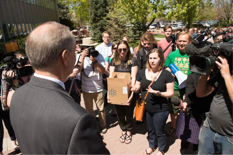 "Leah Hogsten  |  The Salt Lake Tribune Care2 petition campaign writer Kelsey Bourgeois talks briefly with BYU's Academic Vice President Brent Webb, who accepted the signatures.  Care2 petition supporters delivered 60,000  petition signatures to Brigham Young University's Abraham O. Smoot administration building, Wednesday, April 20, 2016 to protest the school's ""Honor Code"" and to ask the school to add an immunity clause shielding sexual assault victims from Honor Code investigations."