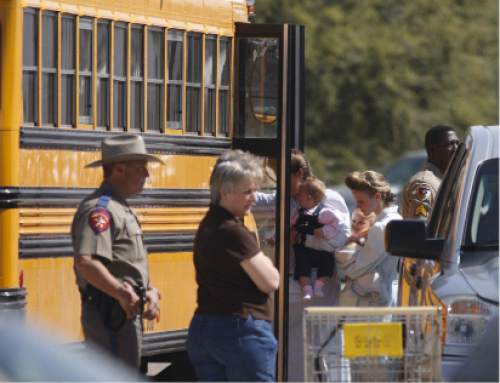 Trent Nelson  |  The Salt Lake Tribune  FLDS women and children from the YFZ ranch are escorted by Texas Child Protective Services workers and Schleicher County Sheriff's deputies from the First Baptist Church's Fellowship Hall to buses in this April 2008 photo.