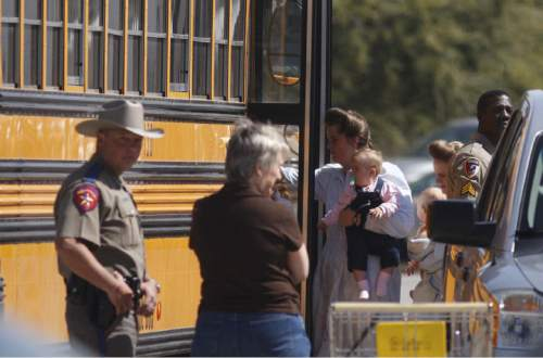 Trent Nelson  |  The Salt Lake Tribune  FLDS women and children from the YFZ Ranch are escorted by Texas Child Protective Services workers and Schleicher County Sheriff's deputies from the First Baptist Church's Fellowship Hall to waiting buses Sunday, April 6, 2008.