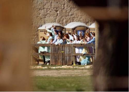 Trent Nelson  |  The Salt Lake Tribune  FLDS women stand behind a fence at Fort Concho, waving to other FLDS women in another building. Texas Child Protective Services said they have taken 401 children from the YFZ Ranch into protective custody as of Monday, April 7, 2008 and brought them to Fort Concho.