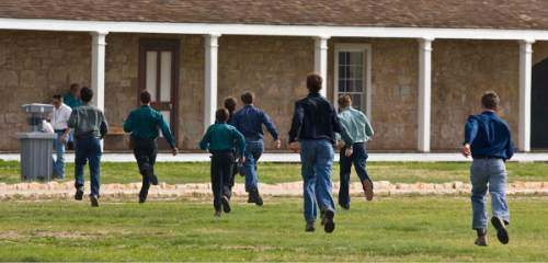 Trent Nelson  |  The Salt Lake Tribune  A group of FLDS boys run through a field at Fort Concho, where they are being held by Texas Child Protective Services Tuesday, April 8, 2008. CPS says they have taken 401 children from the YFZ Ranch into protective custody and brought them to Fort Concho.