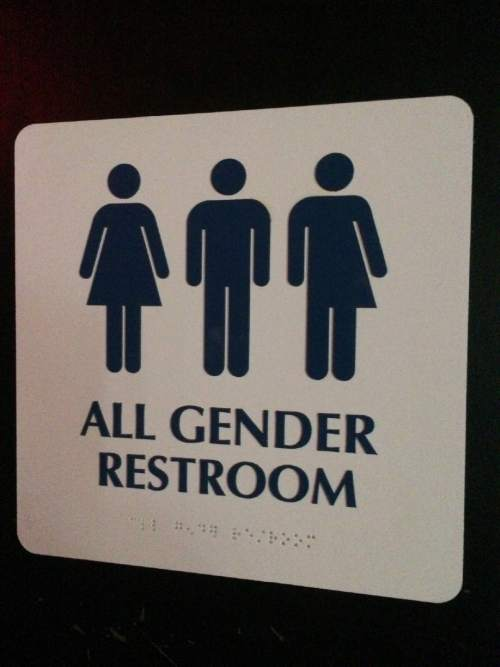 """This May 11, 2014 photo shows an """"All Gender Restroom"""" sign outside a bathroom in a bar in Washington. Confrontations have flared across the country over whether to protect or curtail the right of transgender people to use public restrooms in accordance with their gender identity. (AP Photo)"""