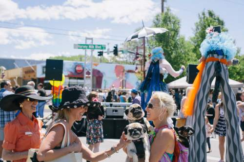 SALT LAKE CITY, UTAH - May 14, 2016: Street fest goers take selfies and dance with the newly unveiled sign  for Harvey Milk Boulevard in Salt Lake City on Saturday, May 14, 2016.