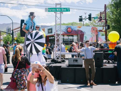 SALT LAKE CITY, UTAH - May 14, 2016: Street fest goers take selfies with the new Harvey Milk Boulevard sign unveiled at the dedication ceremony for Harvey Milk Boulevard in Salt Lake City on Saturday, May 14, 2016.