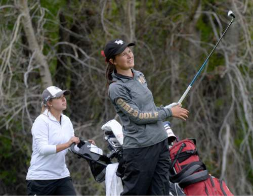Al Hartmann     The Salt Lake Tribune Lone Peak's Lauren Taylor watches her ball after drive on front nine hole on the final day of the of the 5A girls' golf tournament on the Lake Course at Wasatch Mountain State Park Monday May 17.  Davis High School's Jessica Sloot, left.