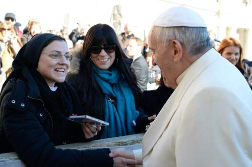 "In this photo provided by the Vatican newspaper L' Osservatore Romano, Pope Francis greets Sister Cristina Scuccia as she presents him with her compact disk at the end of his weekly general audience in St. Peter's Square at the Vatican, Wednesday, Dec. 10, 2014. After winning the Voice of Italy singing contest, the Ursuline nun launched her first album ""Sister Cristina"" last month, after a single also included in the album, with her version of Madonna's ""Like a Virgin"". (AP Photo/L'Osservatore Romano, ho)"