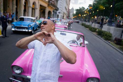 """FILE - In this May 3, 2016, file photo, U.S. Actor Vin Diesel flashes a heart-in-hand to the crowd ahead of the presentation of fashion designer Karl Lagerfeld's """"cruise"""" line for fashion house Chanel, along Paseo del Prado street in Havana, Cuba. The mostly foreign audience arrived in specially hired classic American cars. Havana residents had to watch from behind police lines more than a block away.  (AP Photo/Ramon Espinosa, File)"""