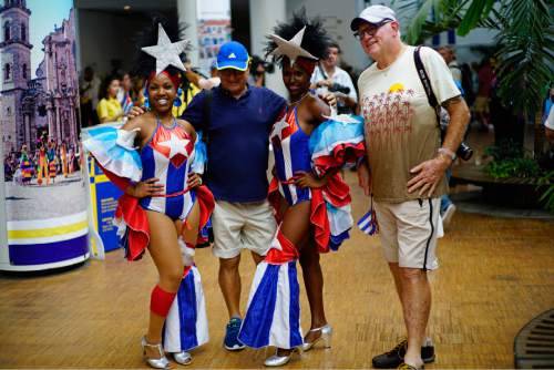 FILE - In this May 2, 2016 file photo, passengers from Carnival's Adonia cruise ship pose with Cuban dancers upon arrival from Miami, in Havana, Cuba. Around the world, television viewers watched prosperous-looking Americans greeted by trays of rum drinks and Afro-Cuban dancers in skimpy Cuban flag-patterned bathing suits. For many Cubans, it was a spectacle uniting the worst exotic stereotypes about their country with disrespect for a symbol of independence. (AP Photo/Ramon Espinosa, File)