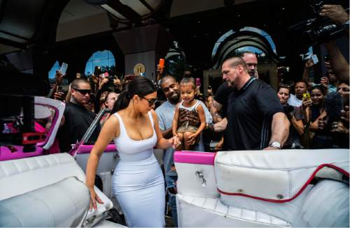 FILE - In this May 5, 2016 file photo, American reality-show star Kim Kardashian gets into a classic American car next to her husband, rap singer Kanye West and their daughter North West, in Havana, Cuba. Artists, writers and intellectuals who believe deeply in Cuba's opening to the world are questioning their government's management of an onslaught of big-money pop culture. (AP Photo/Ramon Espinosa, File)