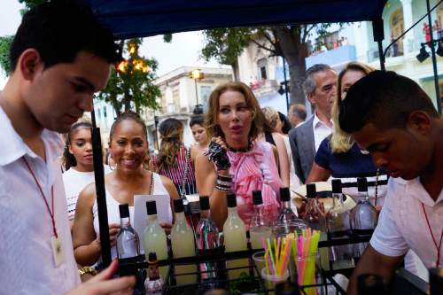 "FILE - In this May 3, 2016 file photo, people have cocktails prepared for them before the presentation of fashion designer Karl Lagerfeld's ""cruise"" line, for fashion house Chanel along Paseo del Prado street in Havana, Cuba. A year and a half after the U.S. and Cuba declared detente, and a month after President Barack Obama visited Havana, it seemed as if the world of global commerce and entertainment had finally landed on Cuba with full force. But people's personal offense at being held far from the events began translating into skepticism about whether their country's hot new status would help improve their lives. (AP Photo/Ramon Espinosa, File)"