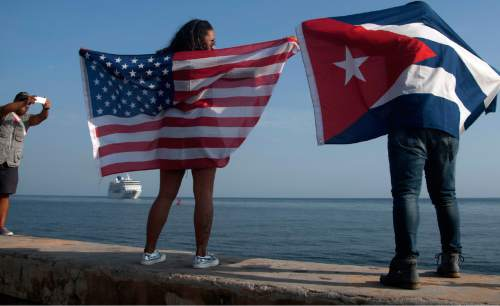 "FILE - In this May 2, 2016 file photo, Yaney Cajigal, left, holds out a Stars and Stripes, and Dalwin Valdes holds a Cuban national flag, as they watch the arrival of Carnival's Adonia cruise ship from Miami, in Havana, Cuba, the first step toward a future in which thousands of ships a year could cross the Florida Straits, long closed to most U.S.-Cuba traffic. Cuba's official Union of Writers and Artists complained that the cruise ship reception with trays of rum and Afro-Cuban dancers in skimpy bathing suits offered ""a deplorable sight to those visiting our country for the first time."" (AP Photo/Fernando Medina, File)"