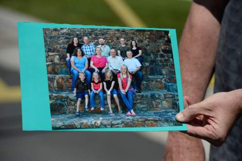Francisco Kjolseth | The Salt Lake Tribune Richard Massey, a family spokesperson for missing UTA worker 63-year-old Kay Porter Ricks, holds up a family photograph of Kay, center right, with his family. Kay's body who was found Tuesday in Wyoming.