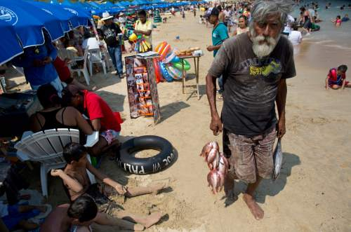 In this May 13, 2016 photo, a fisherman tries to sell his fresh catch to beach goers on Caletilla beach in Acapulco, Mexico. Violence gripping this once-glamorous resort has upsurged in the last months scaring away what international tourism remained. (AP Photo/Enric Marti)
