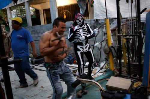 "In this April 23, 2016 photo, members of the Lucha Libre wrestling group who call themselves, ""Guerreros del Cuadrilatero-Club Soley""or Club Soley Wing Warriors, train for a show on the back patio of a barbershop in the Las Cruces neighborhood of Acapulco, Mexico. Residents of Acapulco's slums suffer the worst of the violence despite the high-profile tourist-quarter killings. New police chief Max Saldana said he thinks the gangs ""have retreated up into the 'colonias,'"" or slums, where few tourist dollars ever arrive. (AP Photo/Enric Marti)"