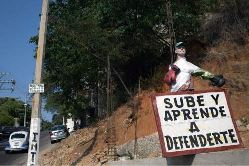 "This May 12, 2016 photo shows a sign advertising a boxing school with a message that reads in Spanish; ""Come on up and learn to defend yourself,"" alongside a road leading to the marginal neighborhoods of Acapulco, Mexico. The upsurge in killings has made Acapulco one of Mexicoís most violent places, scaring away what international tourism remained and recently prompting the U.S. government to bar its employees from traveling here for any reason. (AP Photo/Enric Marti)"