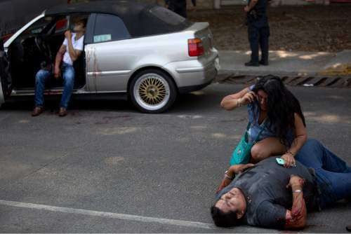 In this May 13, 2016 photo, a woman talks on a phone over a wounded Edgar Osvaldo Vega, as Pedro Gracias sits in a car bleeding, waiting for assistance after being shot by unknown gunmen while driving near Caleta beach in Acapulco, Mexico. Police showed up, but when no ambulance arrived, relatives or friends simply bundled the men into private vehicles to take them to the hospital. Police marked spent shell casings with cut-off plastic soda bottles, but there was no sign of any in-depth investigation. (AP Photo/Enric Marti)