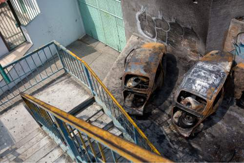 "In this May 11, 2016 photo, two burnt out Volkswagen Beatle shells, colloquially referred to as ""Vochos"", sit near an overpass on a road leading to the neighborhoods overlooking Acapulco, Mexico. According to neighbors the cars were set on fire about two years ago, during a shootout. (AP Photo/Enric Marti)"