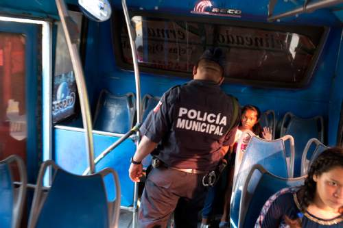 "In this May 10, 2016 photo, a girl riding a bus puts up her hands as a local policeman conducts a routine search at a checkpoint along the ""costera,"" the seaside boulevard that runs through the hotel zone in Acapulco, Mexico. An upsurge in killings has made Acapulco one of Mexico's most violent places, scaring away what international tourism remained. In response, Mexico has lined the city's coastal boulevard with heavily armed police and soldiers, but successes have been few. (AP Photo/Enric Marti)"