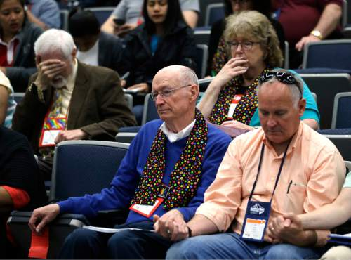 Attendees, two wearing multi-colored scarves in support of LGBT rights, pray after an unscheduled announcement from Bishop Bruce Ough, from the Dakotas-Minnesota church district and president of the Methodist Council of Bishops, concerning the stance of the Methodist church on LGBT rights during the United Methodist Church General Conference in Portland, Ore., Tuesday, May 17, 2016. The church currently bans same-sex marriages and the ordination of clergy who live openly with same-sex partners. (AP Photo/Don Ryan)
