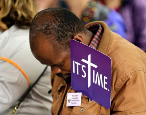 Mpagi Kirumira Michael, from Uganda, holds a sign as he bows his head during a media event where supporters of LBGT rights spoke out against the Methodist Church in Portland, Ore., Monday, May 16, 2016. The United Methodist Church is holding its' annual conference in Portland and is expected to vote sometime this week on their stance concerning their ban on same-sex marriages and on ordaining clergy who live openly with same-sex partners. (AP Photo/Don Ryan)