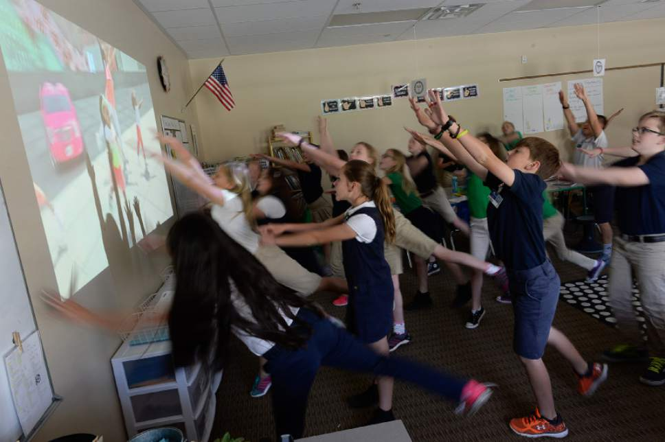 "Francisco Kjolseth | The Salt Lake Tribune  Taking a short ""Brain Break,"" 5h grade students at Ascent Academy in Farmington dance and sing along to a video on the screen. Utah's charter school cottage industry shifts millions of dollars in public funding to private companies."