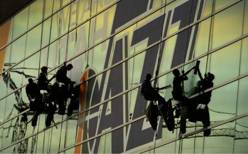 Leah Hogsten  |  The Salt Lake Tribune l-r Mark Harris, Tyson Pacheo, Kenneth Brown, Perry Bates and Dallas Raddatz with High Tech Window Cleaning place new Utah Jazz banners on the windows of Energy Solutions Arena, October 23, 2014.