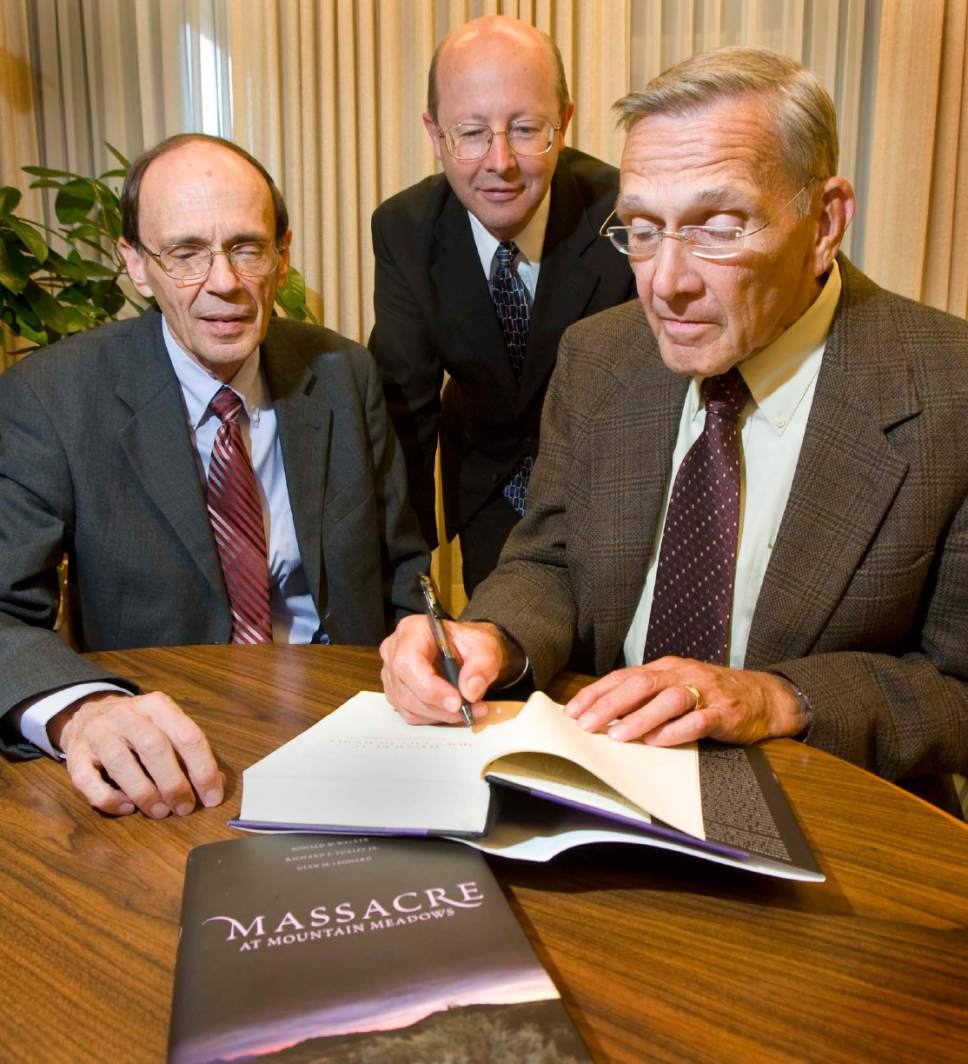 "The authors of ""Massacre at Mountain Meadows."" Glen M. Leonard, Richard E. Turley Jr. and Ronald W. Walker sign a copy of their book on Wednesday, July 30 2008. Paul Fraughton / Salt Lake Tribune"