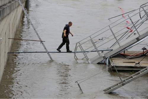 A man balances over a small board to reach a boat on a bank  of the overflowing River Seine in Paris, Thursday, June 2, 2016. Floods are  inundating parts of France and Germany as rivers have broken their banks from Paris to Bavaria. (AP Photo/Markus Schreiber)