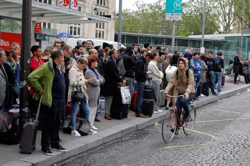 A woman rides a bicycle next to commuters waiting for a bus to Orly Airport during a railway strike in Paris, Thursday, June 2, 2016. Workers at the SNCF national rail authority, whose train service will be crucial to football's Euro 2016 spectators, are on an open-ended strike to protest their working conditions and a controversial government labor reform. (AP Photo/Francois Mori)