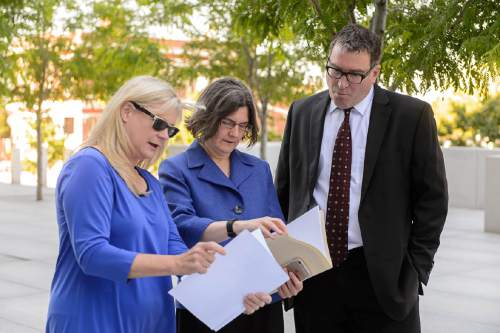 Trent Nelson  |  The Salt Lake Tribune Joan O'Brien of Utah Newspaper Project/Citizens for Two Voices, and attorneys Karra Porter and Dave Richards, look over documents before announcing that the group was dropping its antitrust lawsuit as the sale of The Salt Lake Tribune to Paul Huntsman closed, Tuesday May 31, 2016.
