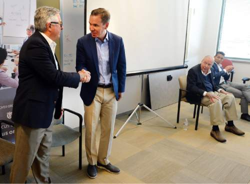 Paul Huntsman shakes hands with Salt Lake Tribune Editor and Publisher Terry Orme, left, after he and his father Jon Huntsman, right, addressed the Salt Lake Tribune staff following a transition of employee benefits meeting at the Tribune offices in Salt Lake City Thursday, May 26, 2016. Paul Huntsman recently purchased the newspaper and the sale should be finalized next week.  (Steve Griffin /The Salt Lake Tribune via AP)